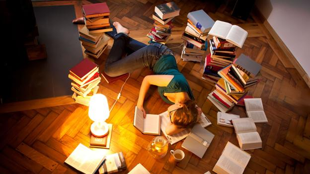 Young woman lying and sleeping on floor, surrounded by books